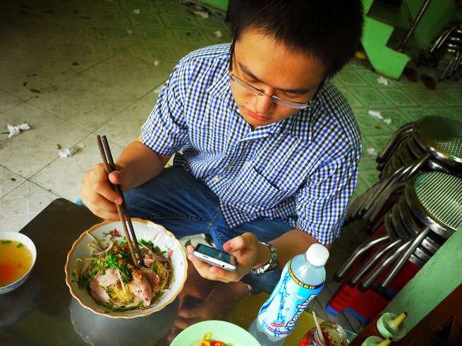 やる気無さげに携帯をいじりながらベトナム麺を食べるLam君。