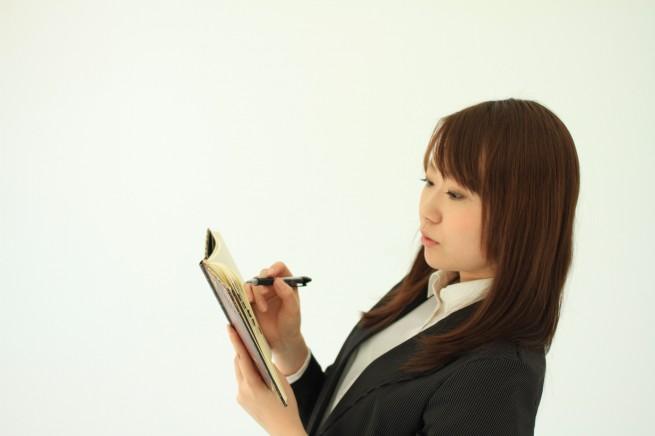 ノートにメモを取っているリクルートスーツ姿の女性の写真