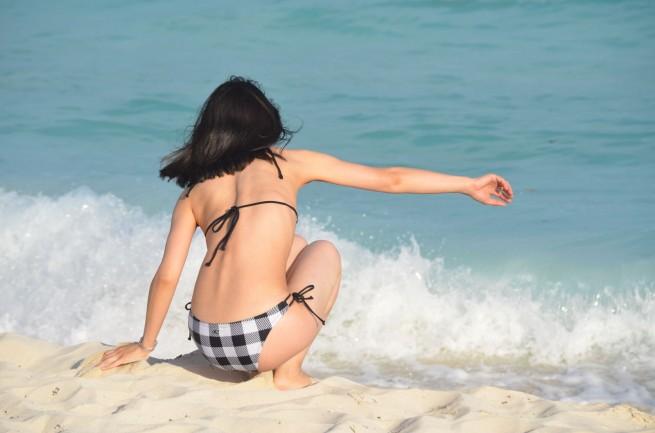 ビーチに座るビキニの女性の後ろ姿の写真