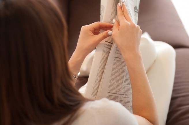 新聞を開こうとしている女性の後ろ姿の写真