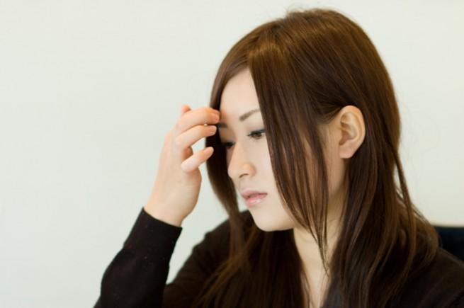 前髪を整えている女性の横顔の写真