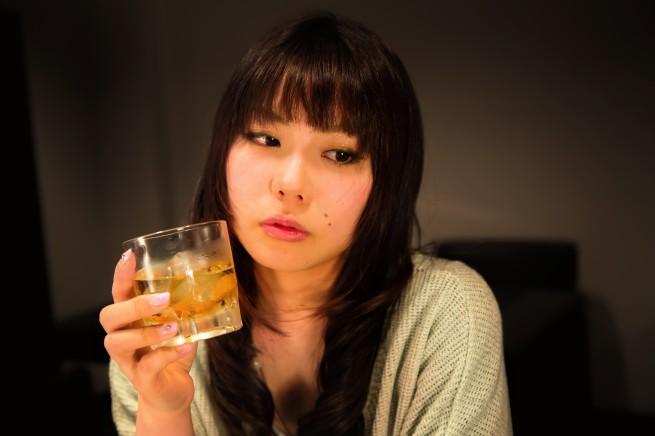 お酒のグラスを片手に物憂げな表情をしている女性の写真