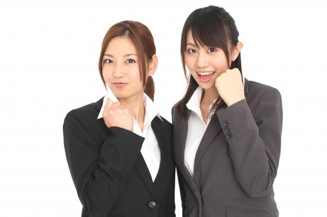 ガッツポーズをしている二人のリクルートスーツ姿の女性の写真