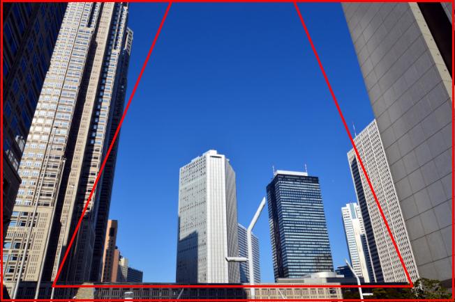 高層ビル群の写真を「三角構図のイメージ」と重ね合わせて解説している画像