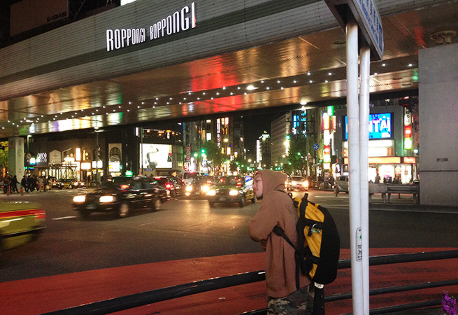 六本木の歩道で待ちくたびれている様子の株式会社LIGのディレクター・まさしの写真