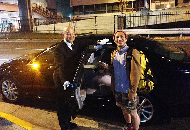 車をバックに株式会社LIGのディレクター・まさしとドライバーが笑顔で立っている写真