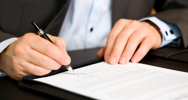 Business person signing a contract, focus on signature.