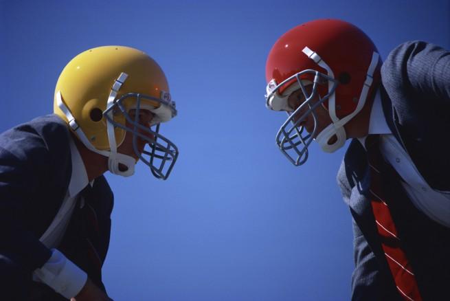 スーツを着てヘルメットをつけた男性2人が向かい合って勝負をしようとしている画像