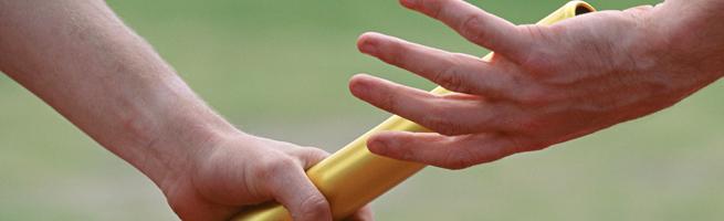 黄色いバトンを渡す手の画像