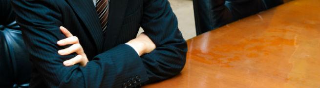 腕を組んでいるスーツ姿の男性の写真
