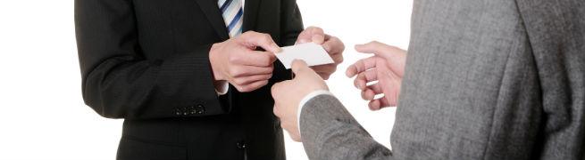 名刺を交換しているスーツ姿の男性2人の写真