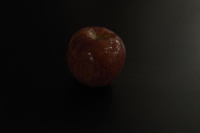 暗い場所におかれたりんごの写真