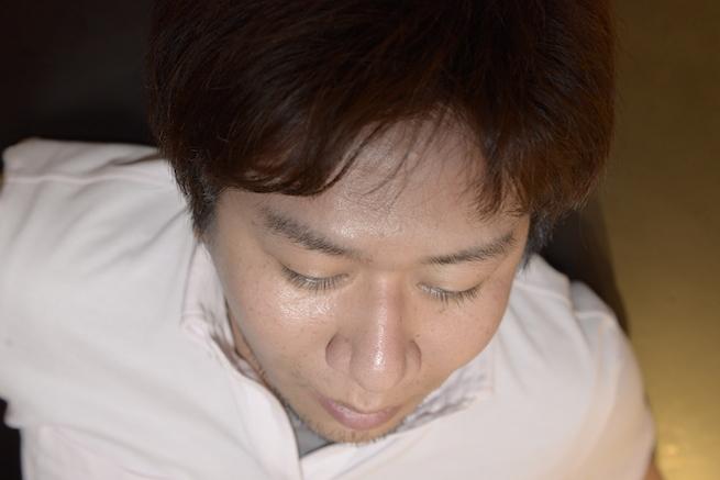 顔に直接フラッシュを当てて撮影した男性の写真