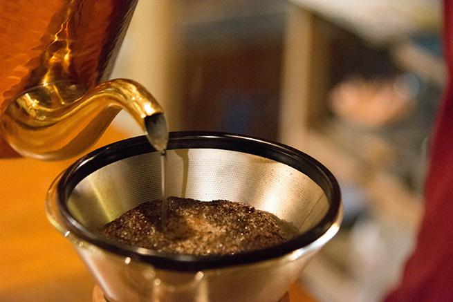 コーヒーフィルタにやかんでお湯を注いでいる写真