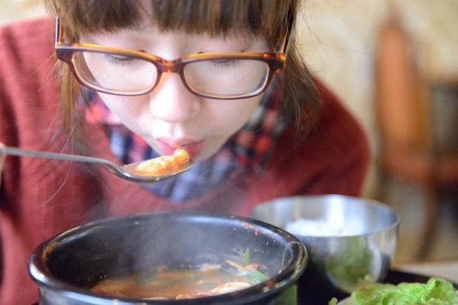 熱い鍋料理を冷ましながら食べようとしている女性の写真