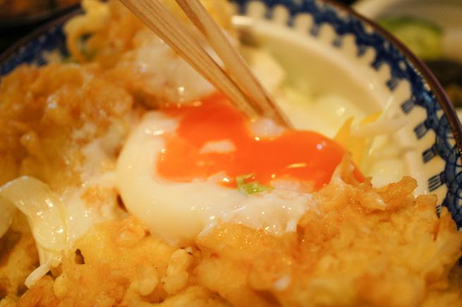 天丼に乗っている半熟卵を箸で崩している写真