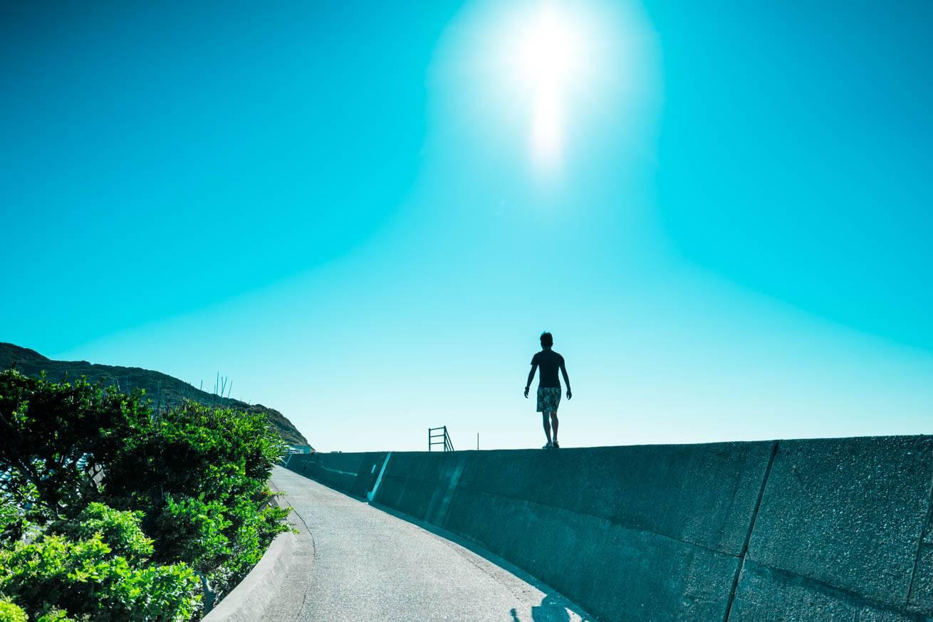 雲一つない青空の下、防波堤の上を歩いている株式会社LIGの社長・吉原ゴウの写真