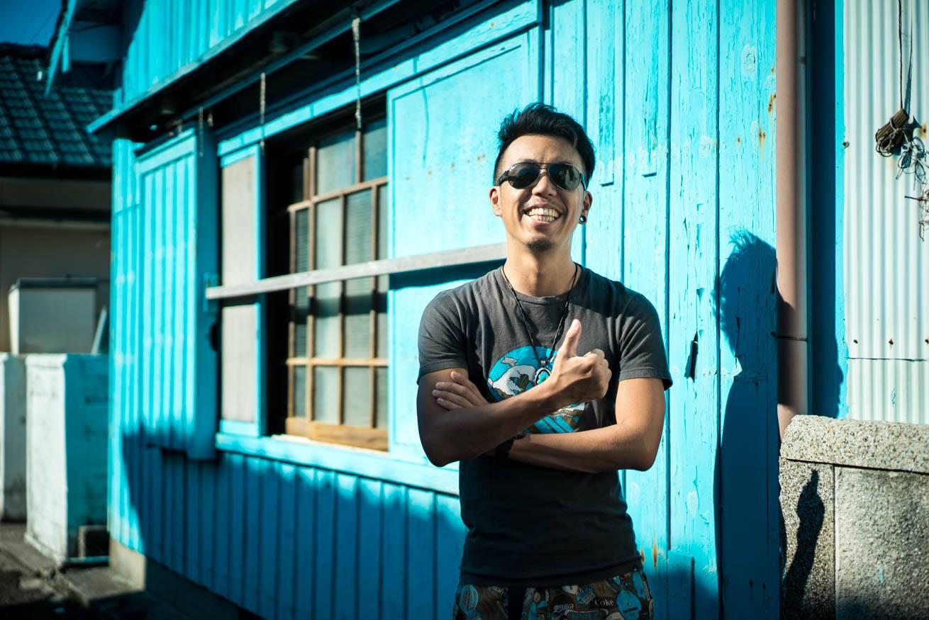 壁が一面ブルーに塗られた家屋の前に立っている株式会社LIGの社長・吉原ゴウの写真