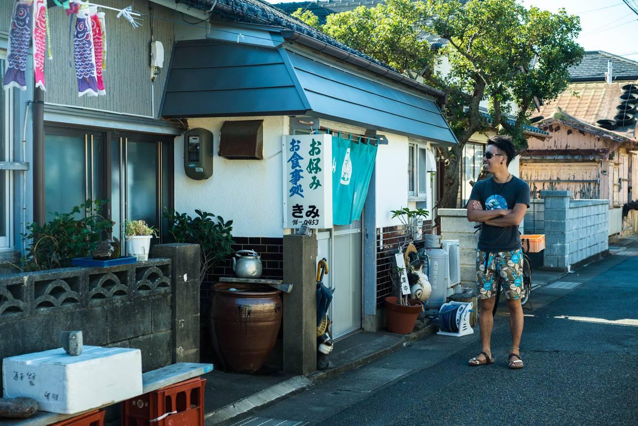 「お食事処」との看板がある小さな店の前に立っている株式会社LIGの社長・吉原ゴウの写真