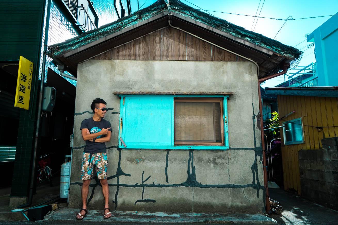 窓枠がブルーに塗られた家屋の前に立っている株式会社LIGの社長・吉原ゴウの写真