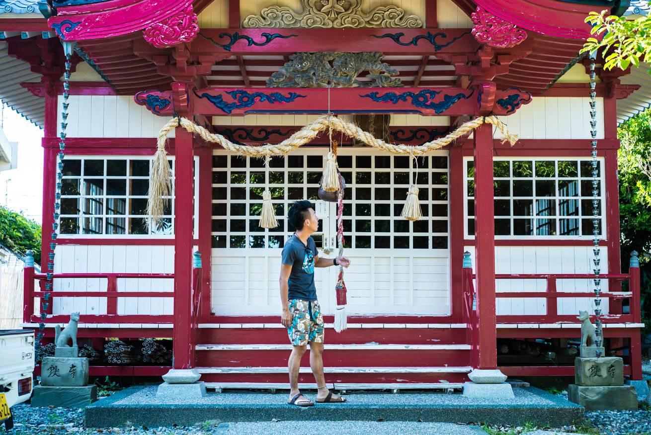 ピンク・ブルー・ホワイトのビビットな配色が施された神社の前に立っている株式会社LIGの社長・吉原ゴウの写真