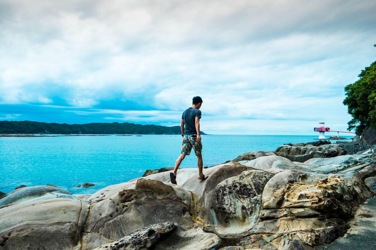 珍しい形の岩の上を歩いている株式会社LIGの社長・吉原ゴウの写真
