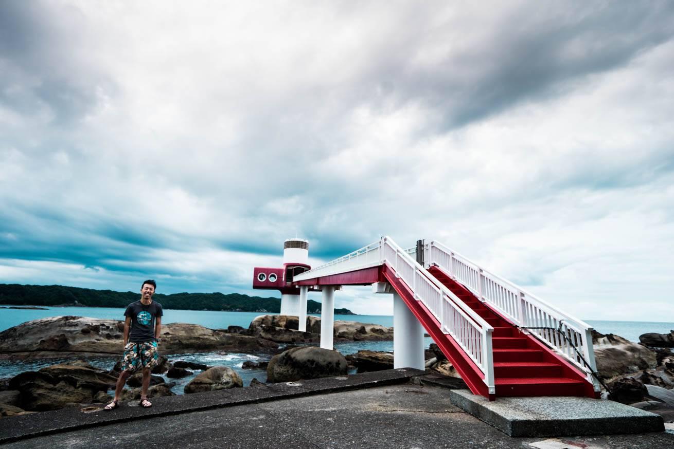 海中に立つ施設に続く、歩道橋の横に立っている株式会社LIGの社長・吉原ゴウの写真