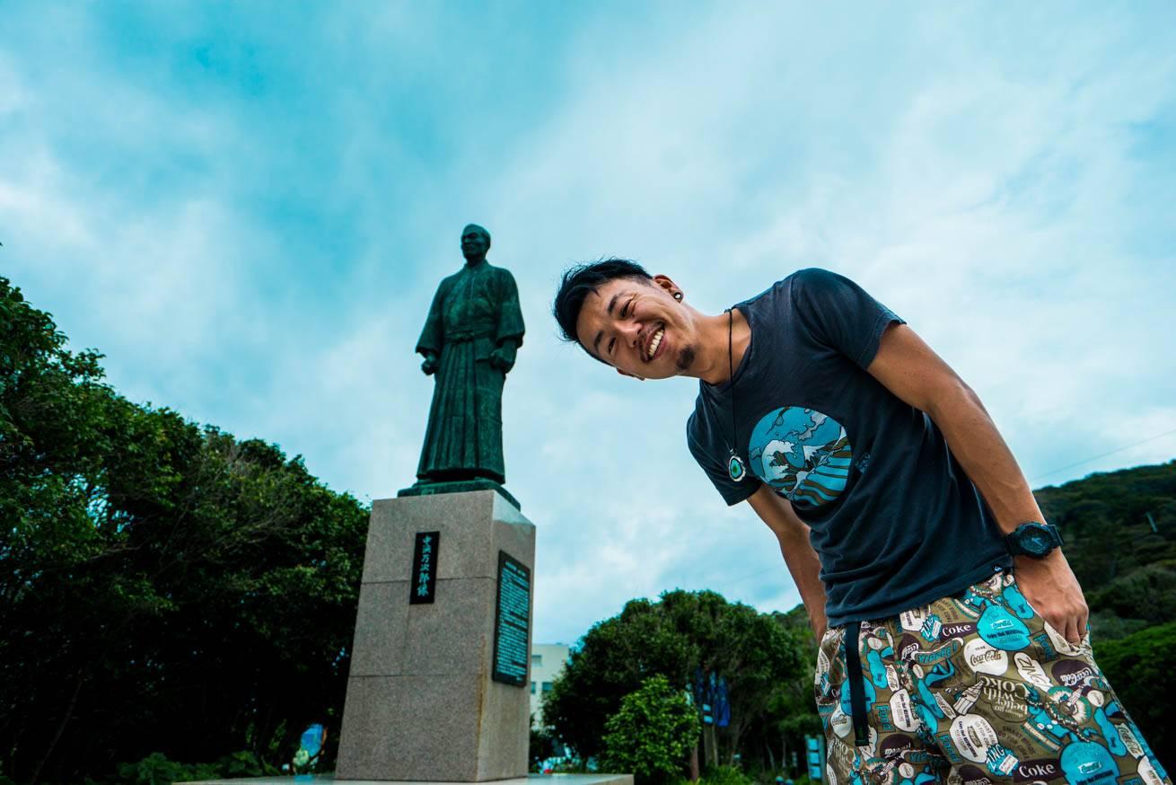 ジョン万次郎の銅像の前に立っている株式会社LIGの社長・吉原ゴウの写真
