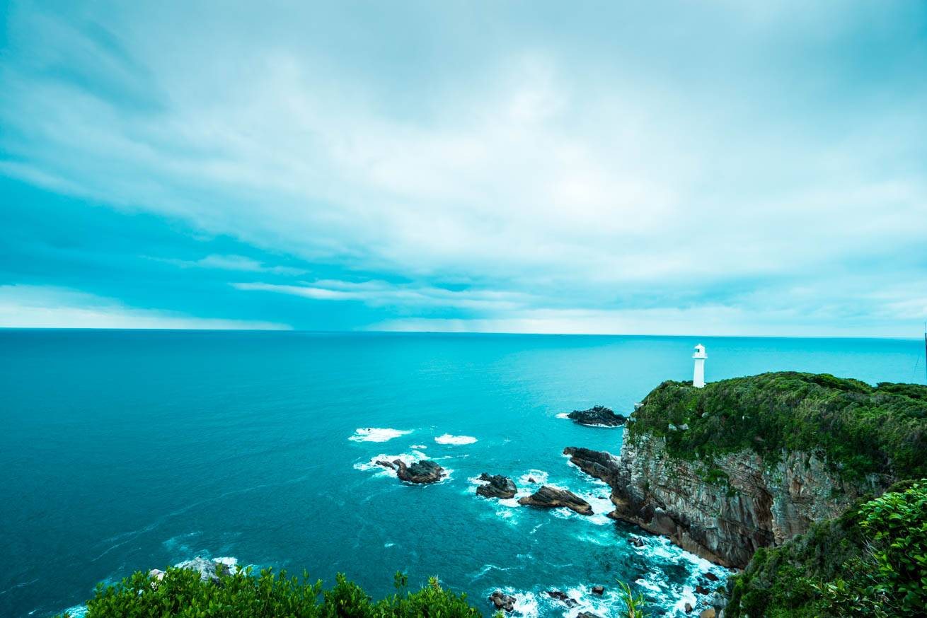 灯台の立つ絶壁・青い海・空が広がる足摺岬からの眺望の写真