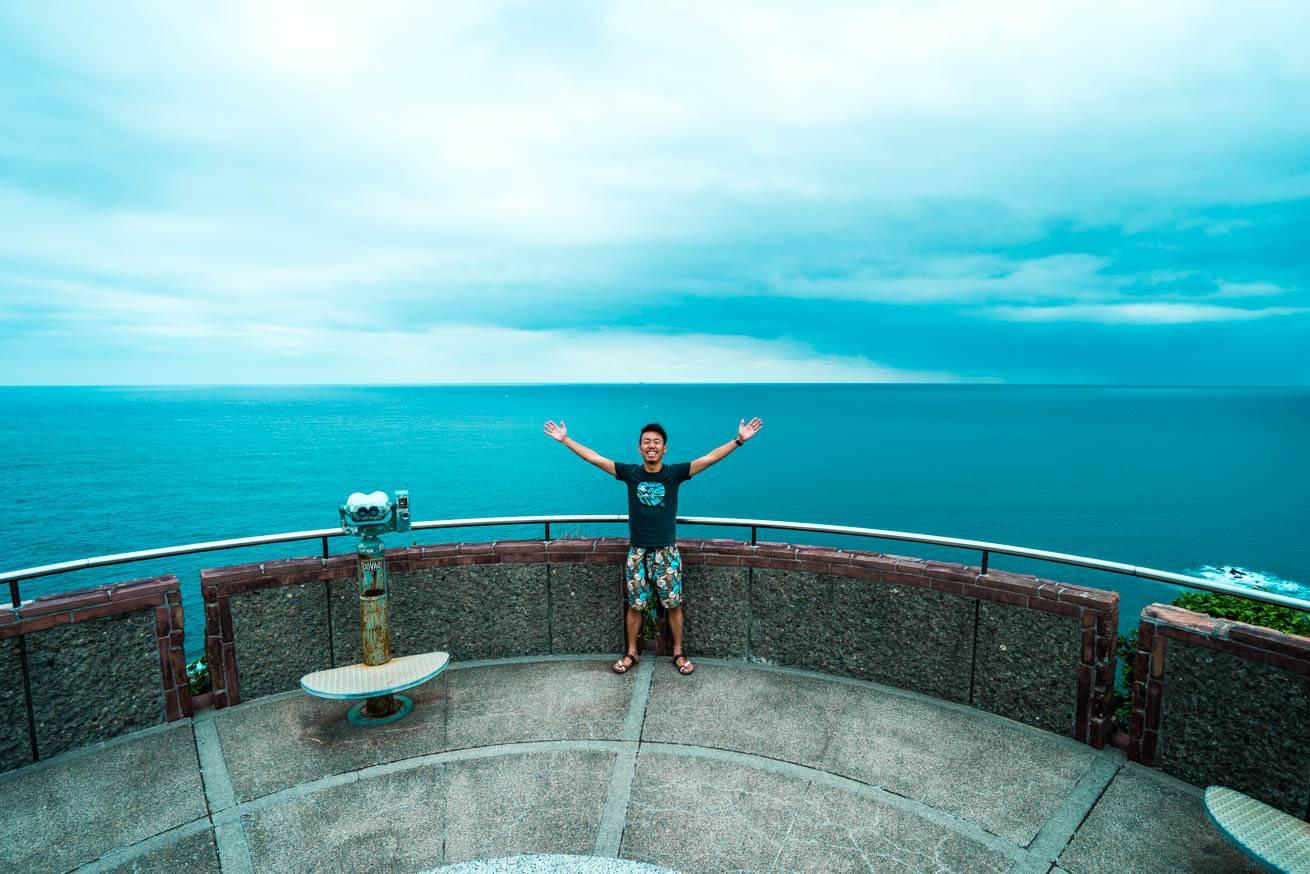 海をバックに両手を広げている株式会社LIGの社長・吉原ゴウの写真