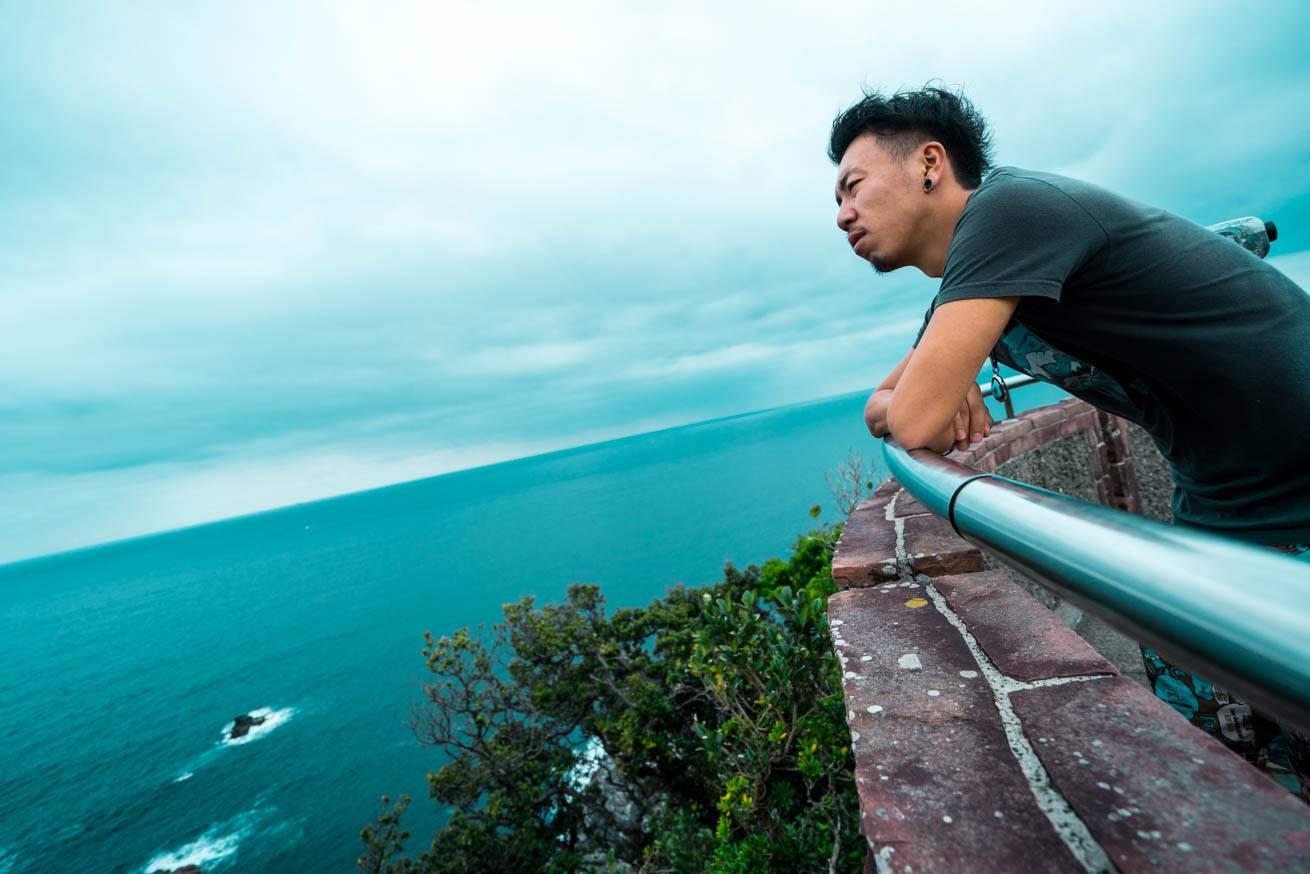 展望台の手すりから海を眺めている株式会社LIGの社長・吉原ゴウの写真