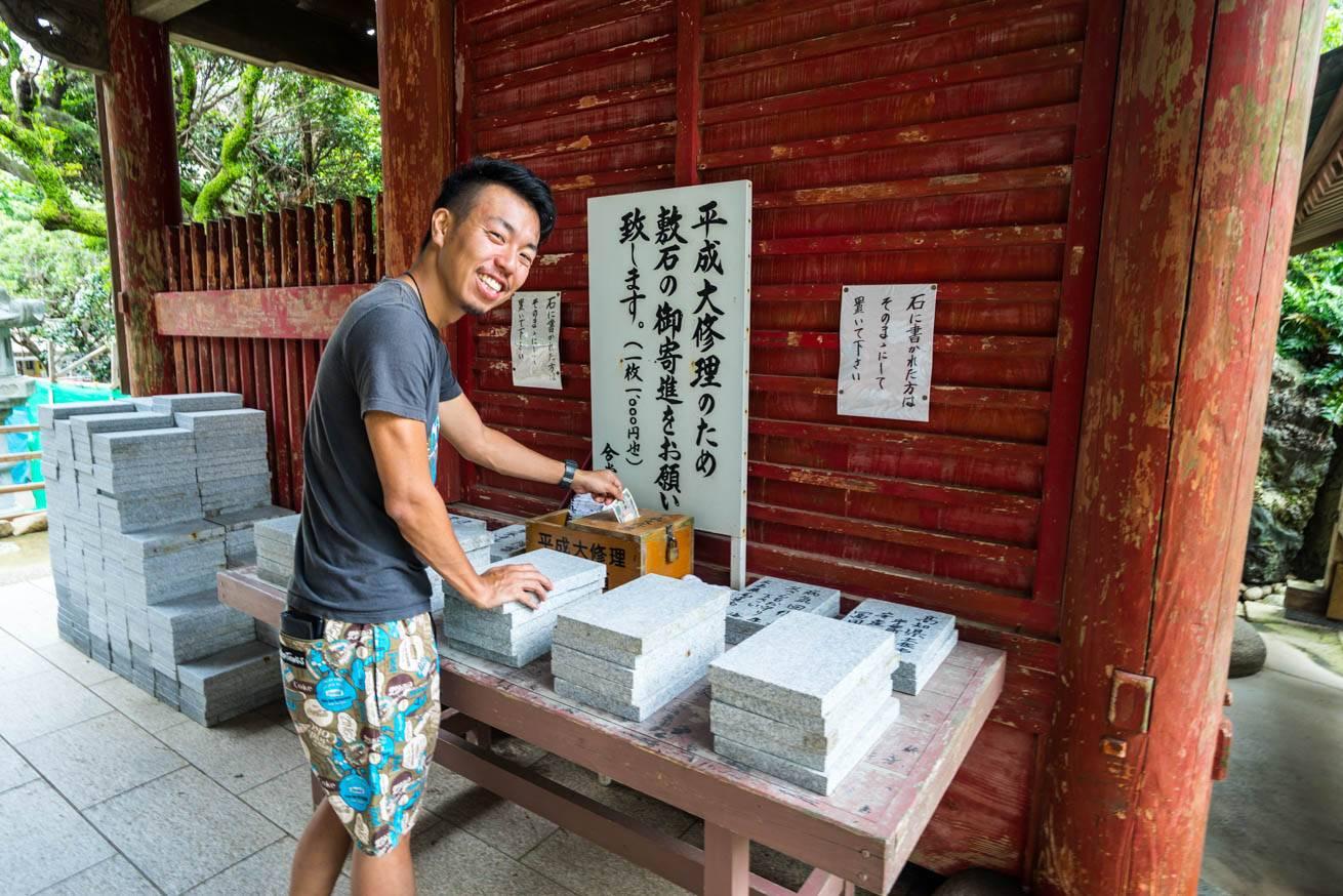 寄進箱にお札を入れている株式会社LIGの社長・吉原ゴウの写真