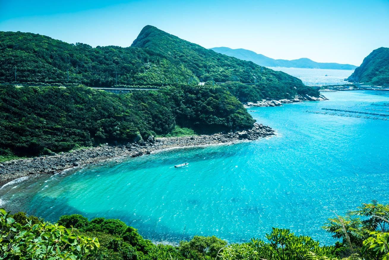 透明度の高い海に、青い空、緑あふれる山々が広がる美しい風景写真