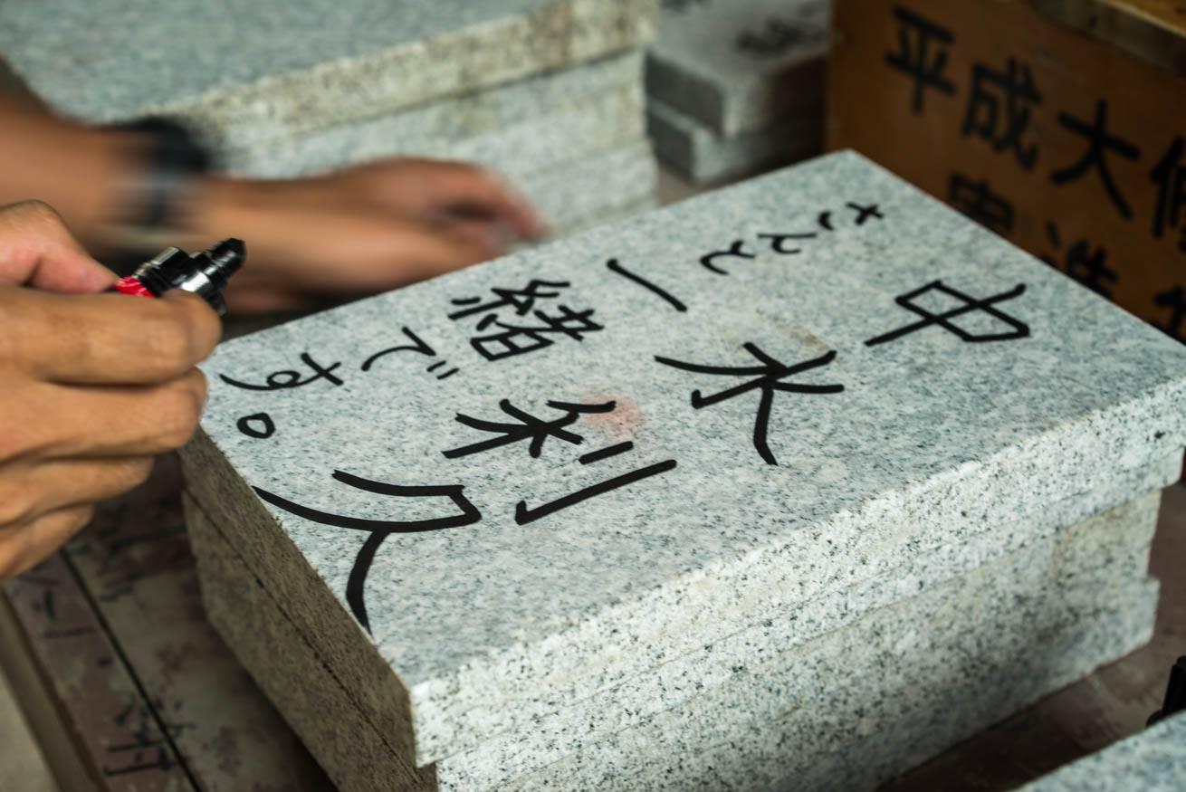 敷石に「中水利久さんと一緒です。」とマジックペンで書いている株式会社LIGの社長・吉原ゴウの写真