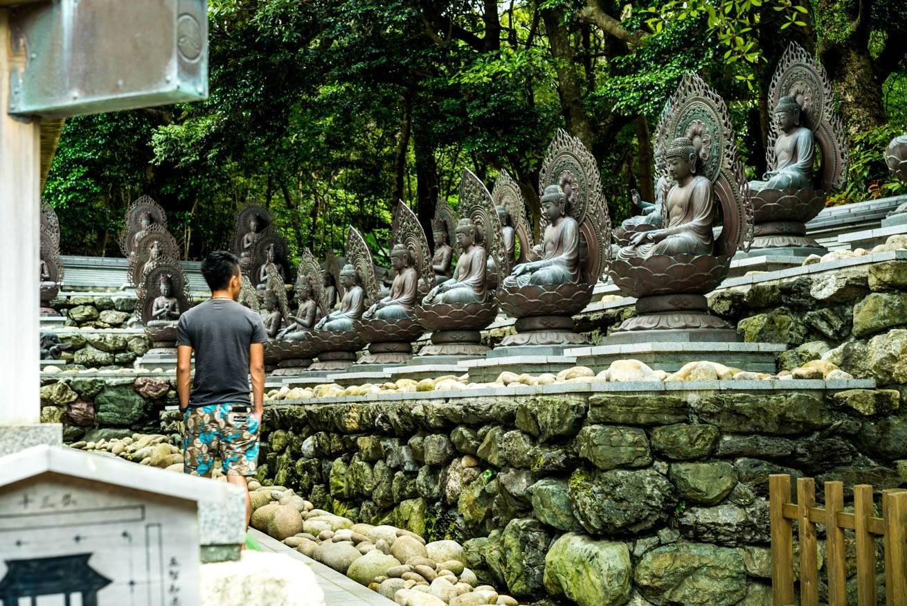 仏像が並んでいる横を歩く株式会社LIGの社長・吉原ゴウの写真