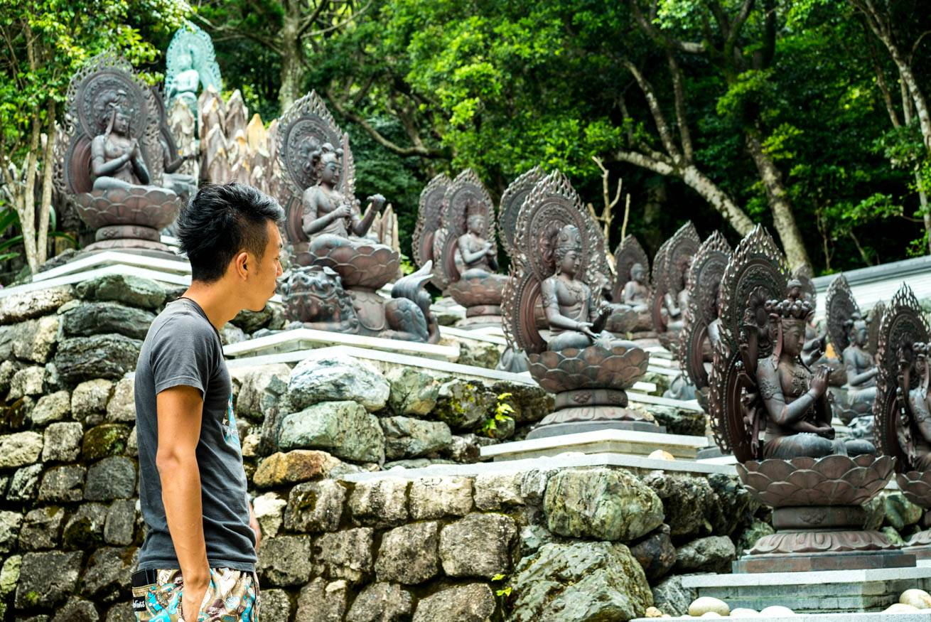 ずらっと並ぶ仏像を見つめている株式会社LIGの社長・吉原ゴウの写真