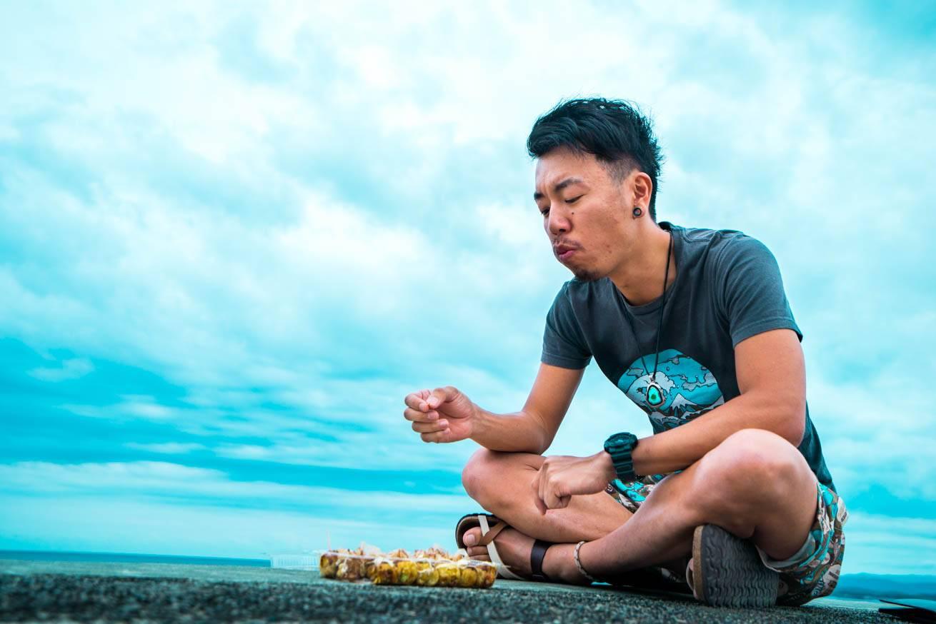 たこ焼きを食べている株式会社LIGの社長・吉原ゴウの写真