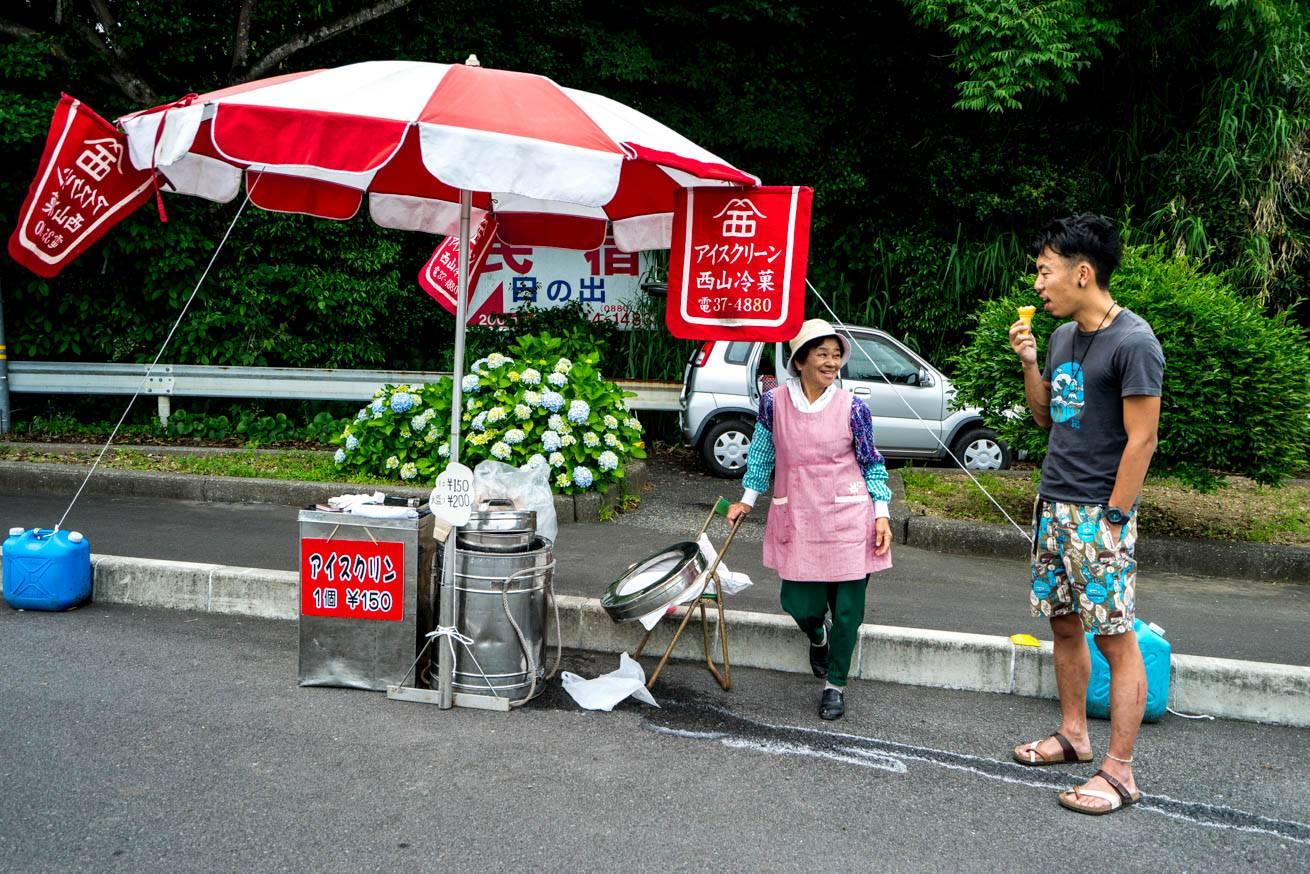 アイスクリン屋台の女性と、アイスクリンを食べている株式会社LIGの社長・吉原ゴウの写真