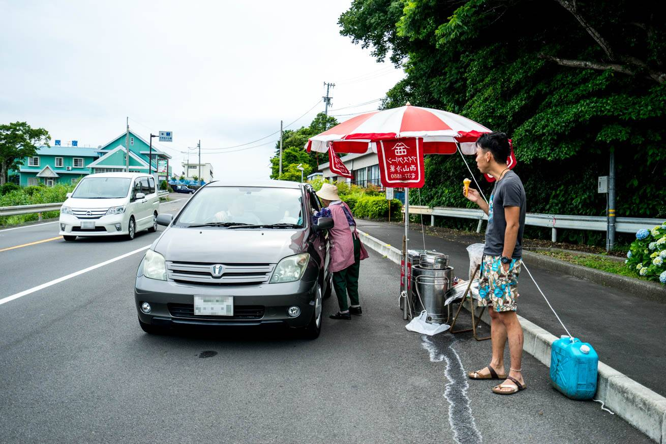車のドライバーにアイスクリンを売る様子を見つめている株式会社LIGの社長・吉原ゴウの写真