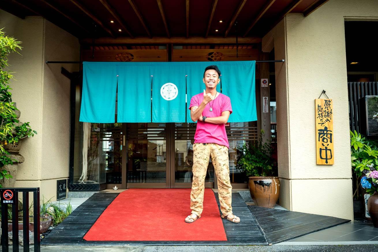 「料亭 濱長」の入り口前に立っている株式会社LIGの社長・吉原ゴウの写真