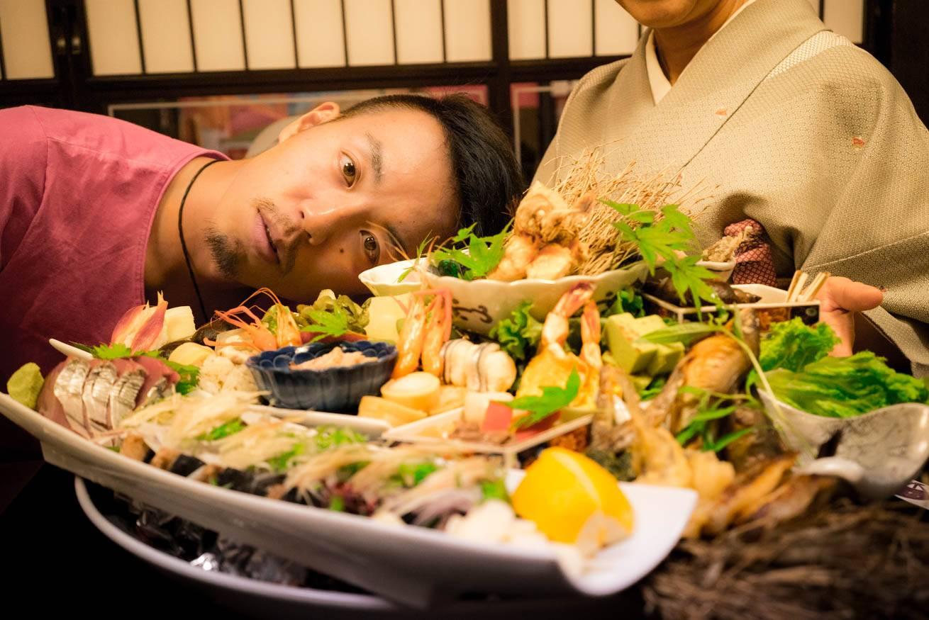 皿に盛られた大量の料理とその奥に映り込む株式会社LIGの社長・吉原ゴウの写真
