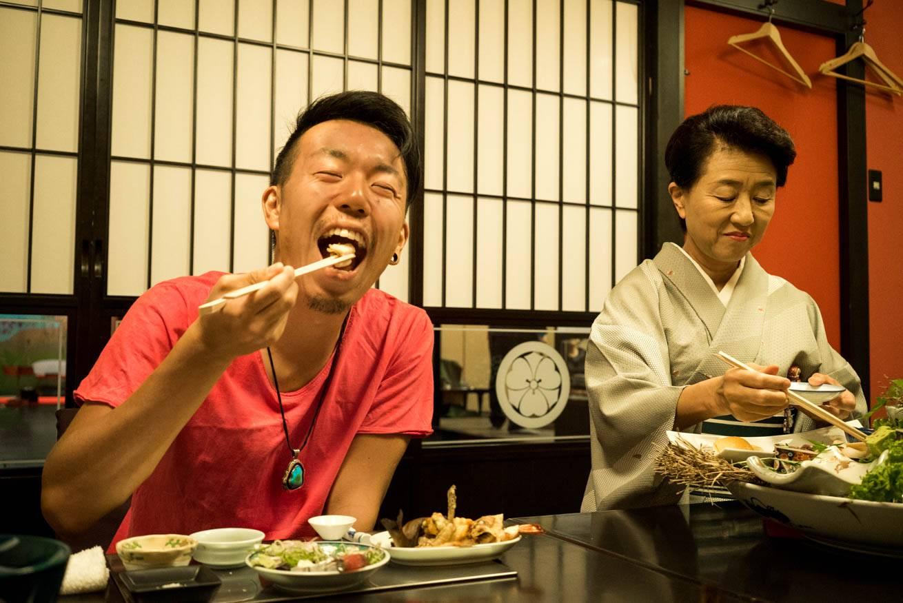中居さんが取り分けてくれた料理を笑顔で食べる株式会社LIGの社長・吉原ゴウの写真