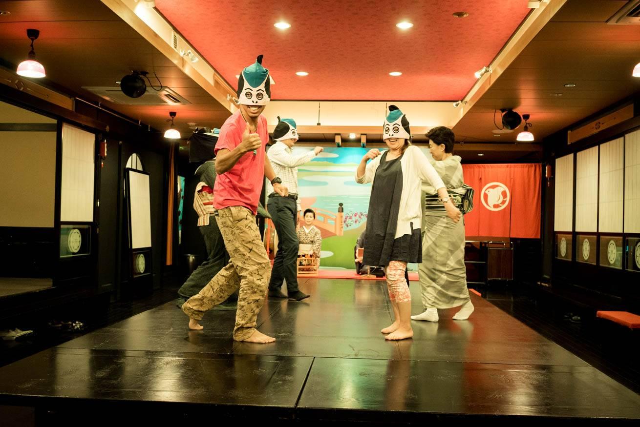 お面を付けてステージの上で踊っている株式会社LIGの社長・吉原ゴウやスタッフの写真