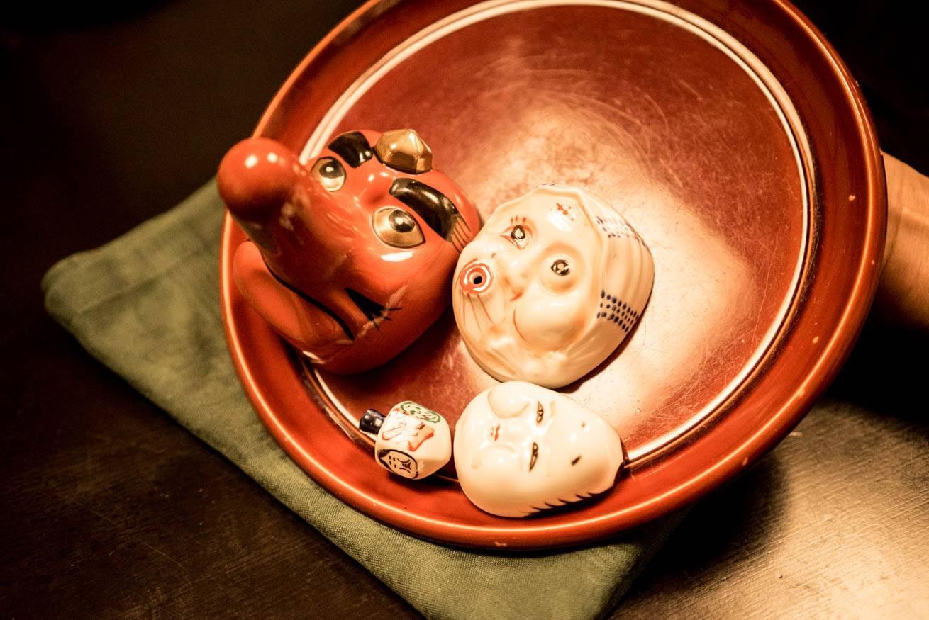 天狗やおたふくの小さなお面が乗った赤い盃の写真