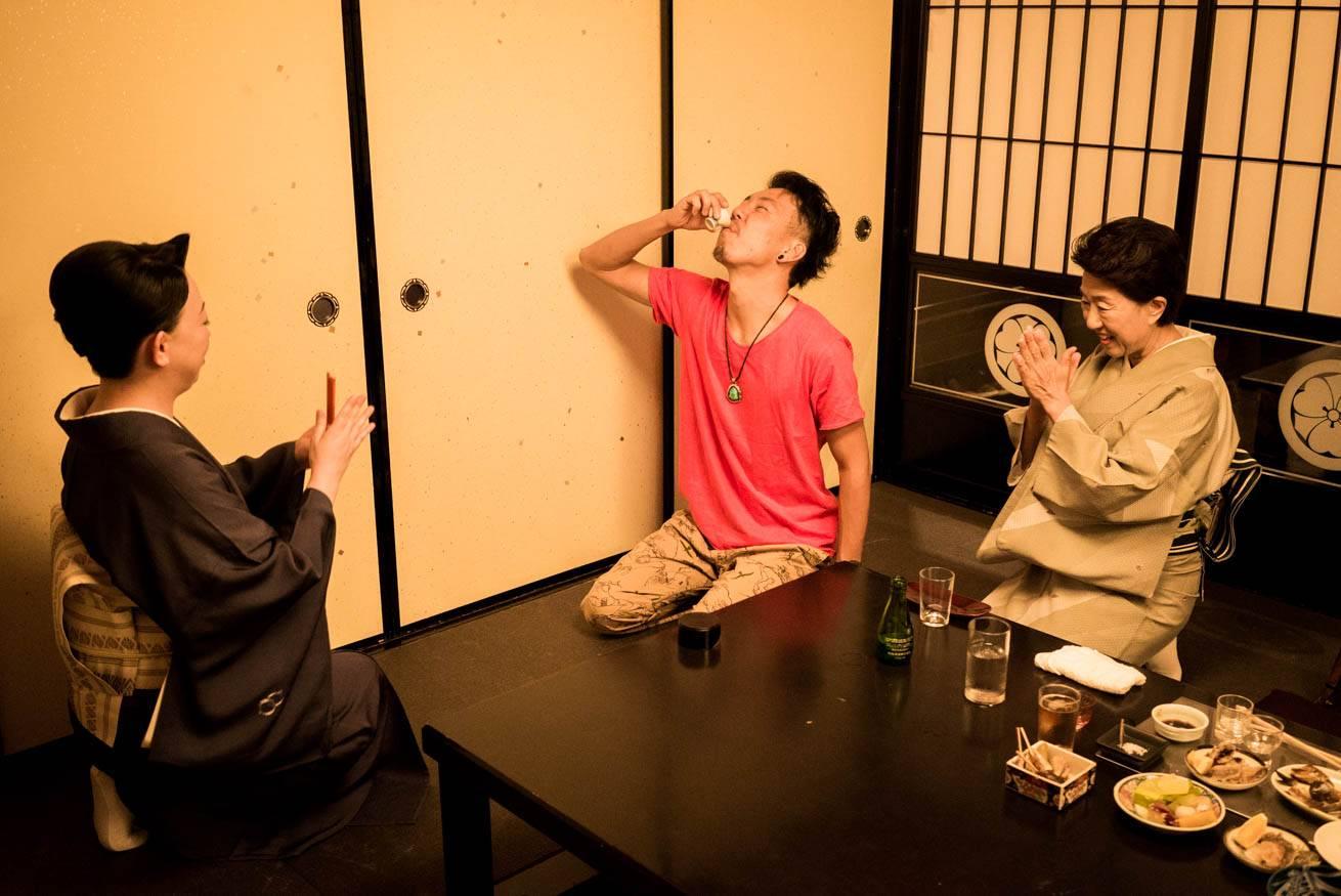 盃のお酒を飲んでいる株式会社LIGの社長・吉原ゴウの写真