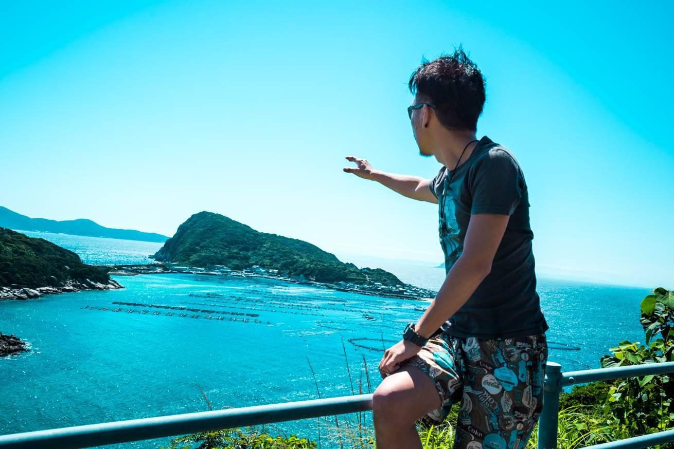 株式会社LIGの社長・吉原ゴウが奥に見える「柏島」という島を指差している写真