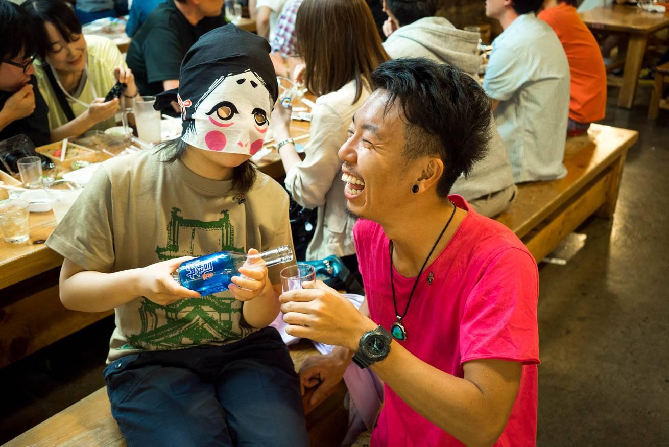 手ぬぐいで顔を隠した女性に酒を注いでもらっている株式会社LIGの社長・吉原ゴウの写真