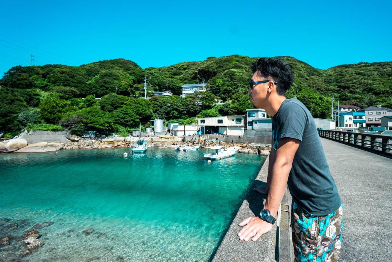 高知県本土と柏島をつなぐ橋の上に立つ株式会社lIGの社長・吉原ゴウの写真