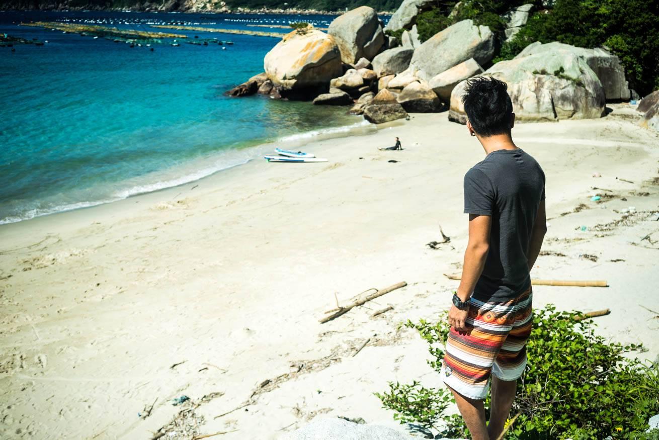 人気のない砂浜に立つ株式会社LIGの社長・吉原ゴウの写真