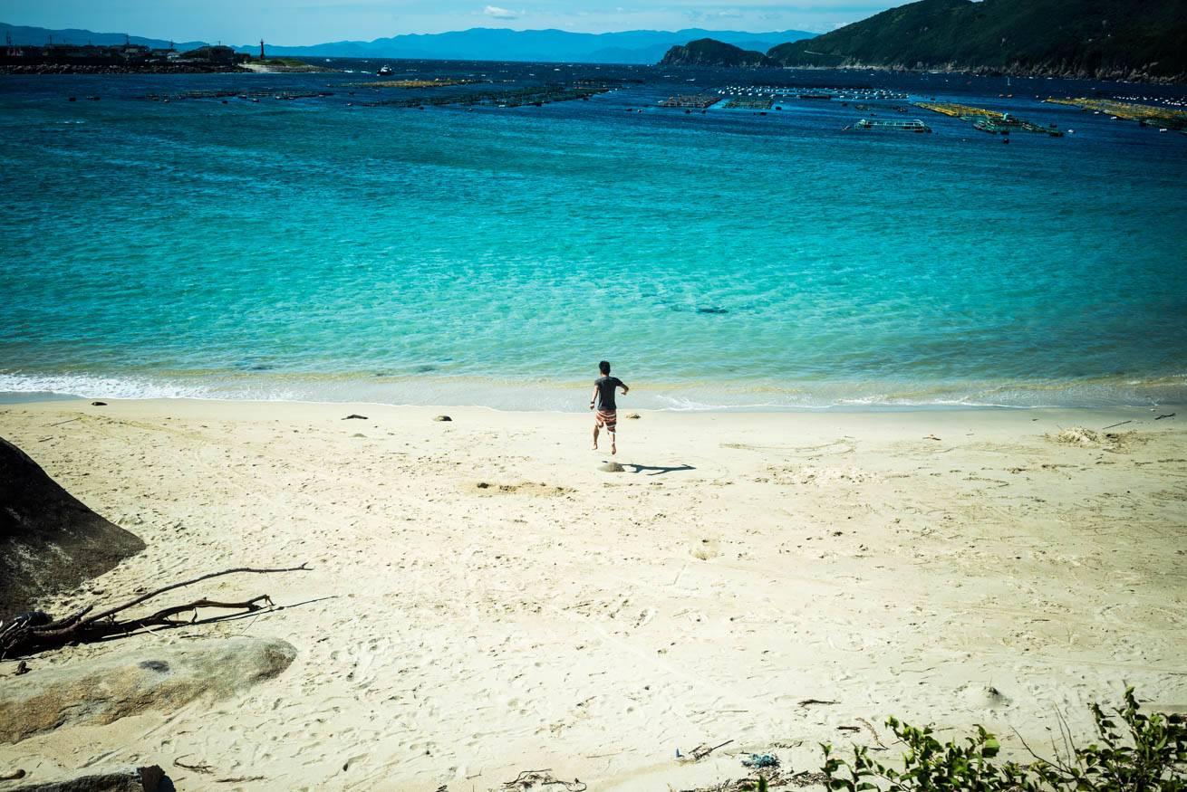 美しい砂浜を海に向かって走っていく株式会社LIGの社長・吉原ゴウの写真